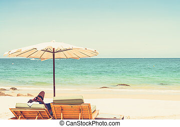Beach chair and umbrella on sand beach. (Vintage filter effect used)