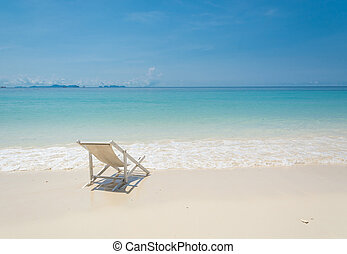 beach chair on beach with blue sky