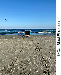 Beach chair on sand near sea