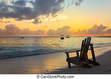 Beach chair on the coast line by sunset