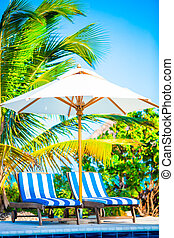 Beach chairs and umbrella at exotic tropical resort - Beach...