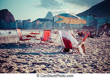 Beach chairs and umbrella on beach in Rio de Janeiro