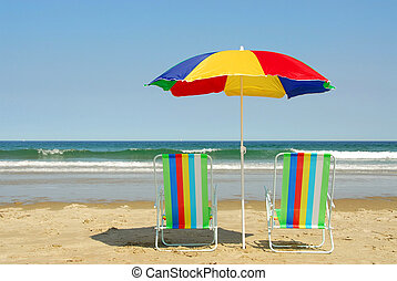 Beach chairs and umbrella on the ocean shore with surf in the background, horisontal