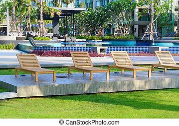 Beach chairs near swimming pool in garden