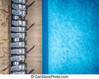 Beach chairs near swimming pool, top view
