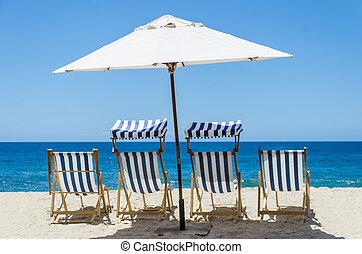Beach chairs near the ocean background