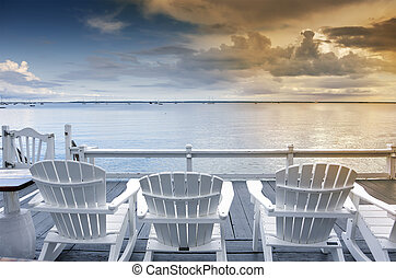 beach chairs overlooking tranquil ocean at sunset on old...