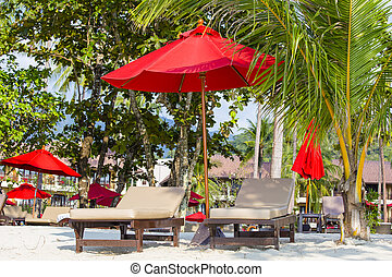 Beach chairs, red umbrella and palm tree on the sand beach in Thailand