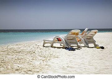 Beach chairs abandoned on the beach.