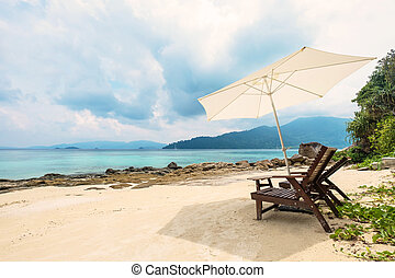 Beach chairs with parasol on beach