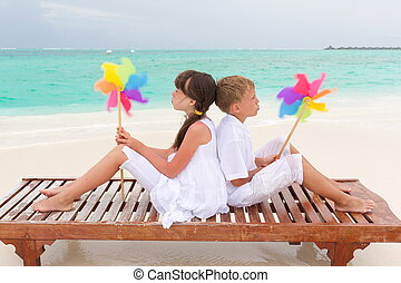 Two children sitting back-to-back on a wooden platform on a beach, holding colorful pinwheels.