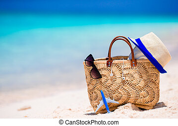 Beach consept - straw bag, hat, sunglasses and towel on white beach
