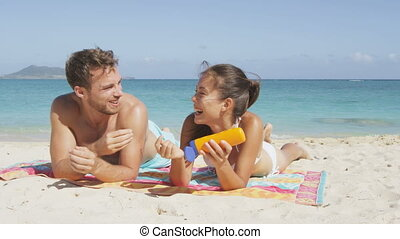 Beach couple sun tanning putting sunscreen suntan lotion on face having fun laughing and relaxing on holiday. Adults, Asian woman and Caucasian man lying down in white sand on beautiful beach.