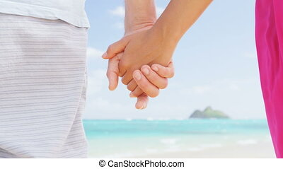 Beach couple in love holding hands on honeymoon. Pink dress, casual beachwear romantic newlyweds people standing on travel summer vacations. RED EPIC SLOW MOTION.