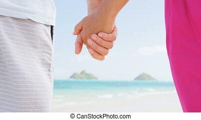 Beach couple in love holding hands on honeymoon. Pink dress, casual beachwear romantic newlyweds people standing on travel summer vacations on Lanikai beach, Oahu, Hawaii, USA with Na Mokulua Islands.