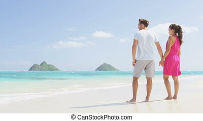 Beach couple looking at ocean view from behind