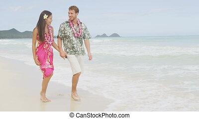 Happy couple on Hawaii vacation walking on beach with Hawaiian leis and Aloha clothing. Caucasian man wearing typical Hawaiian shirt and Asian woman girlfriend in pink sarong fabric sundress. RED EPIC
