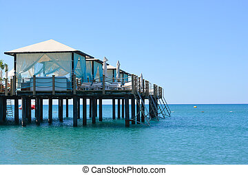 Beach daybed on a suspended dock above the blue sea