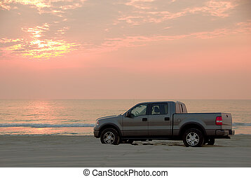 A pickup truck drives on the beach at sunrise on the Outer Banks near Corrolla, North Carolina.