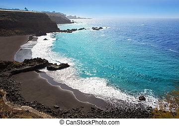 Beach el Bollullo black brown sand and aqua water near...