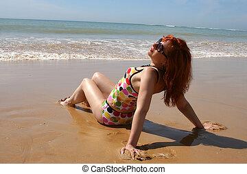 beach enjoyment - woman soaks up the sun at the beach in the...