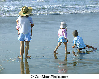 Beach Family - A mom, a baby, and two small children enjoy a...