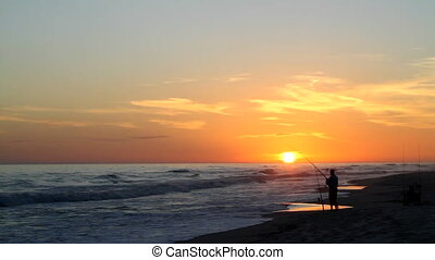 Beach Fisherman At Sunset - Beach fisherman stands by the...