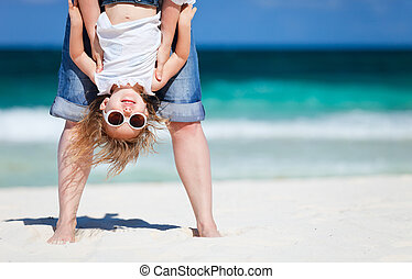 Mother holding her happy smiling daughter upside down having beach fun