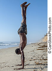 Side view of tall lean shirtless African American man performing handstand on California beach under clear blue sky