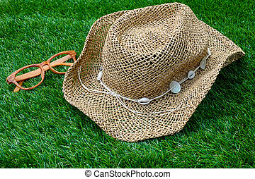 Beach hat and vintage glasses on green grass