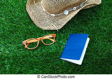 Beach hat ,Passport and vintage glasses on green grass