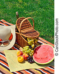 Beach hat, sun glasses, picnic basket with fruits and bottle of wine on the green grass