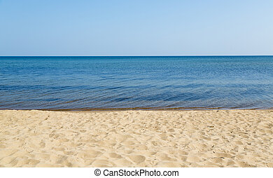 sandy beach with blue water and sky