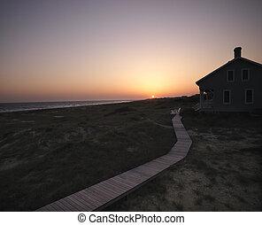 Beach house. - Sunset over coastal beach house with wooden...