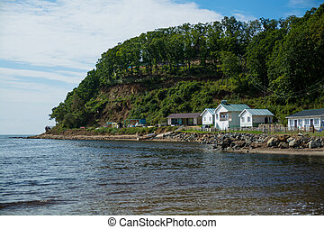 Beach huts on the sea shore under the green hill.