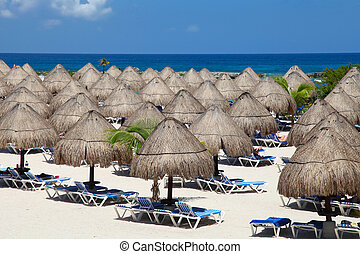 Rows of the palm leaf sun shades on the beach in Riviera Maya