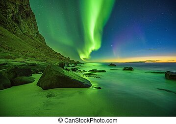 Beach in the Lofoten islands in Norway with strong green northern lights