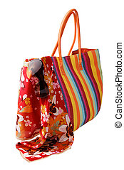 Beach items: colorful striped bag, bright kerchief and straw...