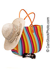 Beach items: colorful striped bag, sunglasses and straw hat