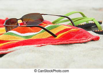 Beach towel, sunglasses and flipflops on white sandy beach