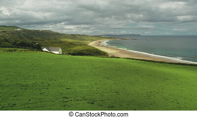 Beach lodge aerial shot: green grass meadow near sea bay and lonely White Rocks. Grey clouds hover over ocean water, sandy shore. Tranquil landscape of nature in Northern Ireland. Footage in 4k, UHD