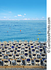 Beach lounge chairs by the sea. Summer vacation theme.