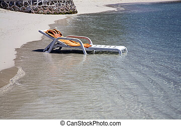 Beach lounger - Water surrounds a forgotten beach lounger as...