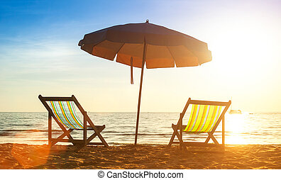 Beach loungers on deserted coast sea at sunrise