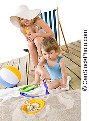 Beach - Mother with child playing with toys in sand