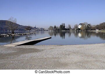 Beach of Albigny and pontoon on Annecy lake with view of the city