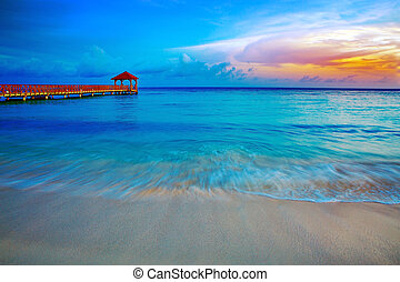 Beach of caribbean sea and wooden pier .