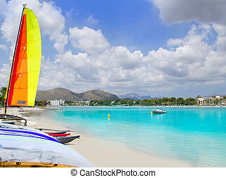Beach of Puerto de Alcudia in Mallorca with hobie cat and kayak on Balearic Islands Spain