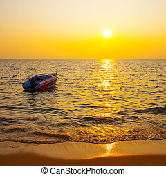 Beach of tropical resort and boat in the sea at sunset