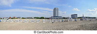 panoramic view of the beach of  Warnemuende with the Hotel Neptun and rows of white beach chairs, Germany